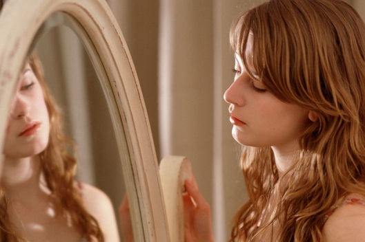 Young-woman-looking-in-mirror